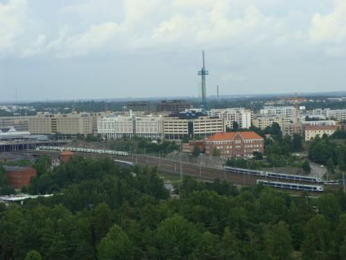 Helsinky - pohled z věže u olympijského stadionu směrem k výstavišti na vlaky nedaleko zastávky Passila (na obr.vlevo za mostem).